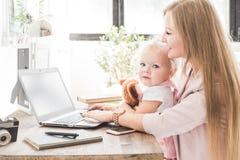 Giovane donna di affari che lavora a casa dietro il computer portatile con un piccolo bambino Area di lavoro scandinava creativa  fotografie stock