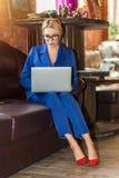 Giovane donna di affari che lavora seduta online sul sof? fotografia stock libera da diritti