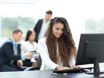 Giovane donna di affari che lavora in un ufficio facendo uso del computer con il co Immagine Stock Libera da Diritti