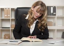 Giovane donna di affari che legge un libro sul lavoro Fotografia Stock Libera da Diritti