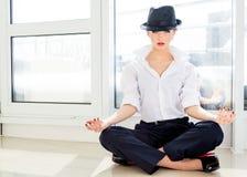 Giovane donna di affari che medita camicia bianca d'uso, cappello in ufficio Fotografia Stock Libera da Diritti