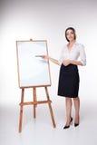 Giovane donna di affari che mostra qualcosa sui precedenti bianchi Immagine Stock Libera da Diritti