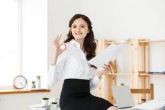 Giovane donna di affari che mostra segno giusto con il documento della tenuta e seduta nell'ufficio moderno Fotografia Stock