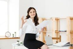 Giovane donna di affari che mostra segno giusto con il documento della tenuta e seduta nell'ufficio moderno Immagini Stock