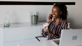 Giovane donna di affari che parla sul telefono cellulare mentre bevendo caff? nell'ufficio video d archivio