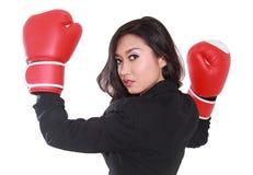 Giovane donna di affari che per mezzo dei guantoni da pugile Immagine Stock