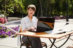 Giovane donna di affari che per mezzo del computer portatile Immagini Stock Libere da Diritti