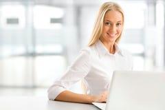 Giovane donna di affari che per mezzo del computer portatile all'ufficio Immagini Stock Libere da Diritti