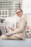 Giovane donna di affari che per mezzo del computer portatile che tiene il suo telefono Fotografie Stock Libere da Diritti
