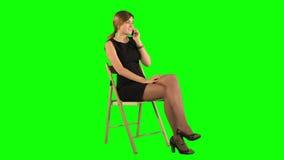 Giovane donna di affari che per mezzo del telefono su un verde stock footage