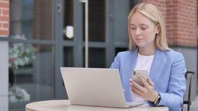 Giovane donna di affari che per mezzo dello smartphone e del computer portatile, sedersi all'aperto stock footage