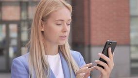 Giovane donna di affari che per mezzo dello smartphone archivi video