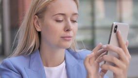 Giovane donna di affari che per mezzo dello smartphone video d archivio