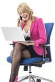Giovane donna di affari che per mezzo di un computer portatile e di un telefono cellulare del cellulare Immagini Stock