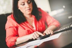 Giovane donna di affari che per mezzo di un calcolatore Fotografia Stock Libera da Diritti