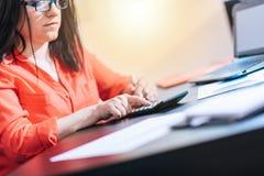 Giovane donna di affari che per mezzo di un calcolatore, effetto della luce Fotografie Stock