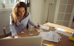 Giovane donna di affari che prende le note da Internet Fotografia Stock