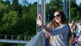 Giovane donna di affari che prende selfie per le reti sociali sulla vacanza sul ponte stock footage