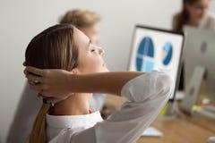 Giovane donna di affari che si rilassa sul lavoro che respira aria fresca, v laterale Fotografia Stock