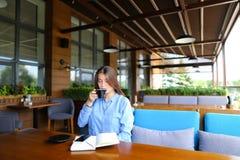 Giovane donna di affari che si siede al caffè con il caffè dello smartphone e del taccuino e di bevanda Immagini Stock