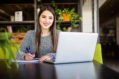 Giovane donna di affari che si siede alla tavola con il computer portatile e che prende le note in taccuino Fotografie Stock Libere da Diritti