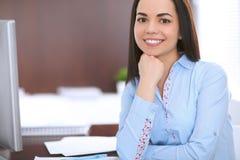 Giovane donna di affari che si siede a alla tavola in ufficio Fotografie Stock