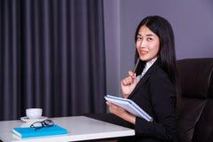 Giovane donna di affari che si siede allo scrittorio e che tiene un libro Immagine Stock