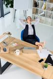 Giovane donna di affari che si siede allo scrittorio in ufficio con i piedi sulla tavola e sulle mani immagini stock libere da diritti
