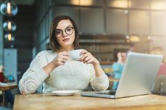 Giovane donna di affari che si siede in caffè alla tavola, al tè bevente e lavorante al computer portatile Lo studente sta studia Immagine Stock Libera da Diritti