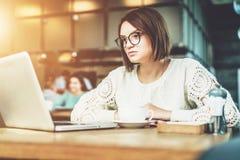 Giovane donna di affari che si siede in caffè alla tavola e che lavora al computer portatile Sulla tazza di caffè della tavola St Fotografia Stock
