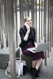 Giovane donna di affari che si siede fuori con il fon del cellulare e del computer portatile Fotografia Stock Libera da Diritti