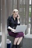 Giovane donna di affari che si siede fuori con il fon del cellulare e del computer portatile Immagine Stock Libera da Diritti