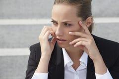 Giovane donna di affari che si siede fuori sulle scale, distogliere lo sguardo Fotografia Stock