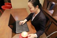 Giovane donna di affari che si siede nella caffetteria alla tavola di legno, caffè bevente Sulla tavola è il computer portatile Fotografia Stock Libera da Diritti
