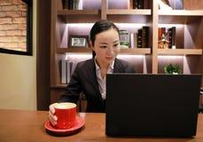 Giovane donna di affari che si siede nella caffetteria alla tavola di legno, caffè bevente Sulla tavola è il computer portatile Immagine Stock Libera da Diritti