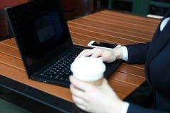 Giovane donna di affari che si siede nella caffetteria alla tavola di legno, caffè bevente Sulla tavola è il computer portatile Fotografia Stock