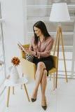 Giovane donna di affari che si siede su una sedia e che tiene compressa in Han fotografia stock