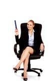Giovane donna di affari che si siede sulla poltrona e che indica su con la grande penna Immagini Stock Libere da Diritti