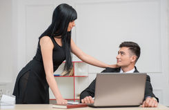 Giovane donna di affari che si siede sulla tavola e che flirta Fotografia Stock Libera da Diritti