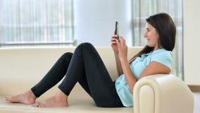 Giovane donna di affari che si siede sullo strato e che per mezzo dello smartphone Ragazza che compera online, blogging, controll stock footage