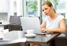 Giovane donna di affari che si siede in un caffè con un computer portatile e un caffè Immagini Stock