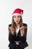 Giovane donna di affari che soffia un bacio con un cappello rosso di natale di Santa Fotografie Stock Libere da Diritti