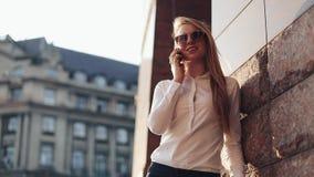 Giovane donna di affari che sta l'edificio per uffici vicino alle vie soleggiate della città e che parla su un telefono cellulare archivi video