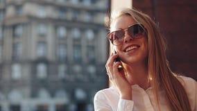 Giovane donna di affari che sta l'edificio per uffici vicino alle vie soleggiate della città e che parla su un telefono cellulare video d archivio