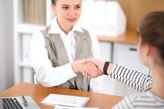 Giovane donna di affari che stringe le mani con un cliente all'ufficio Riuscito concetto di settore assicurativo Immagini Stock Libere da Diritti