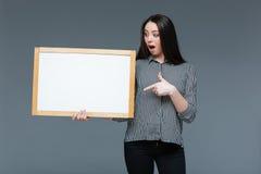 Giovane donna di affari che tiene bordo in bianco Fotografia Stock