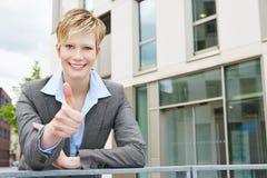 Giovane donna di affari che tiene il suo pollice su Immagine Stock Libera da Diritti