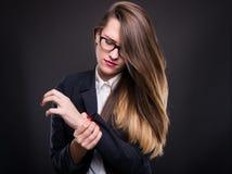 Giovane donna di affari che tiene polso irritato in sua mano fotografia stock libera da diritti