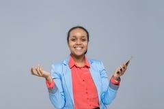 Giovane donna di affari che usando la donna di affari felice di sorriso della ragazza afroamericana dello Smart Phone delle cellu Fotografia Stock