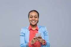 Giovane donna di affari che usando la donna di affari felice di sorriso della ragazza afroamericana dello Smart Phone delle cellu Fotografie Stock Libere da Diritti